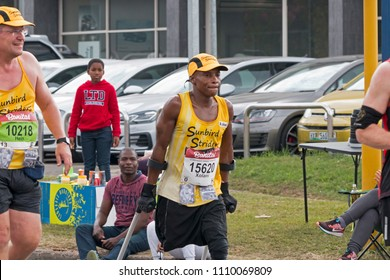 PINETOWN, DURBAN, SOUTH AFRICA - JUNE 10, 2018: Midday unknown spectators runners and amputee Xolani Luvuno using crutches whilst competing in the 2018 Comrades Ultra marathon