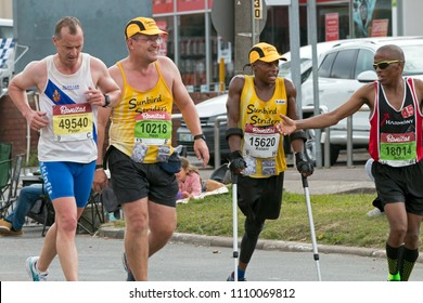 PINETOWN, DURBAN, SOUTH AFRICA - JUNE 10, 2018: Midday unknown runners and amputee Xolani Luvuno using crutches whilst competing in the 2018 Comrades Ultra marathon