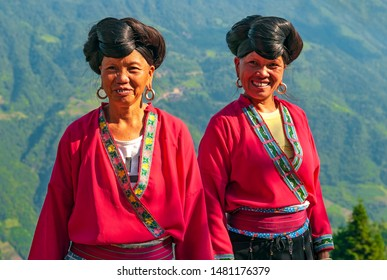 PING AN, CHINA - AUGUST 20, 2011: Smiling long haired women of the Yao ethnic group by the rice terraces of Longsheng Ping An in the Guangxi province, China.