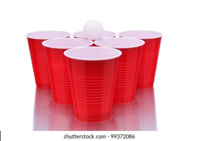 Ping pong ball resting on a group of red plastic cups arranged for playing Beer Pong isolated on a white background with reflection.