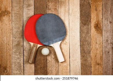 Ping pong paddles and ball on retro wooden background