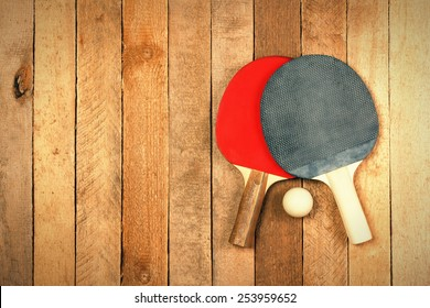 Ping pong paddles and ball on wooden texture with copyspace