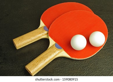 Ping pong paddles and balls on black