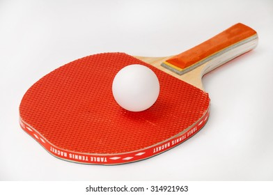 Ping pong racket and white ball.
