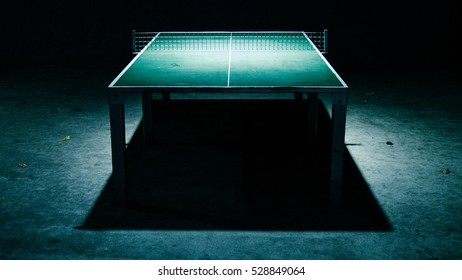 Ping pong table at night with strong shadows