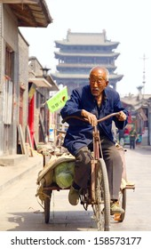 PING YAO, CHINA- APR. 9 2012; Unidentified older man is riding a bicycle at the city of Ping Yao on april 9 2012 ,China.Ping Yao is an well-preserved example of a traditional Han Chinese city.