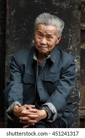 Ping Yao, China - September 20, 2013 : Unidentified old Chinese man sits with his hands on his knees in the streets of the city of Ping Yao which is one of the oldest and historical town in China.