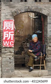 Ping Yao, China - September 20,2013: Unidentified old Chinese woman sits in front of the street toilet and demands entrance fee.