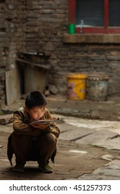 Ping Yao, China - September 20,2013 :Unidentified child studies and reads his homework in a small courtyard of his home