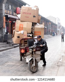 PINGYAO, CHINA - APRIL 7 2017:  A man is seen about to ride his overloaded motorbike in the streets of the old city on April 7, 2017 in Pingyao, China