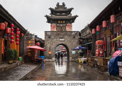 PINGYAO, CHINA - MAY 21, 2018: Tourists and local people in the ancient city of Pingyao in central China, Asia. Rainy weather.
