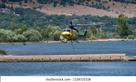 Pinilla del Valle, Spain;  July 27 2018: Firefight helicopter takes water from the Lake to extinguish a near by fire.   Spanish, Helicóptero de bomberos recolecta agua del embalse