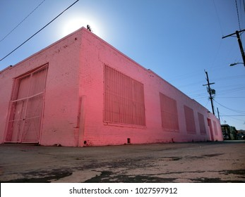 Pink abandoned warehouse exterior with dock doors