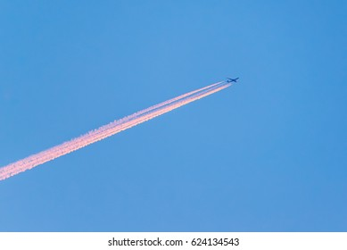 Pink airplane condensation in the sky