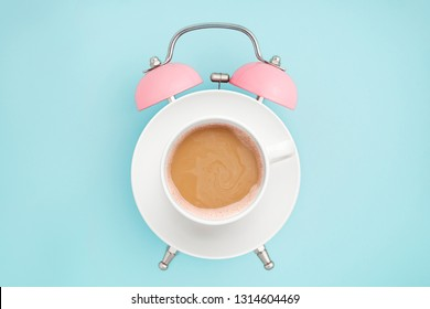Pink alarm clock and coffee cup on blue background. Breakfast time concept. Minimal style