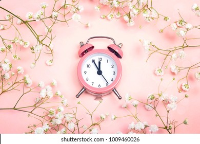Pink alarm clock and delicate little white flowers on pink background. Top view. Time for love and greetings.