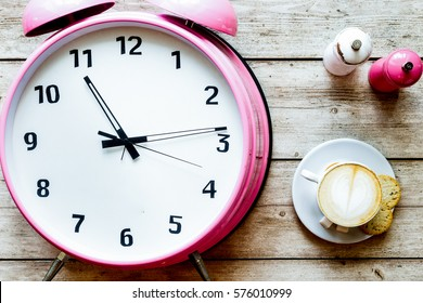 pink alarm clock on wooden table with coffie top view