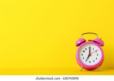 Pink alarm clock on yellow background
