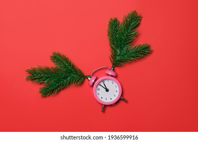 Pink alarm clock with sprigs of Christmas tree, Christmas composition on a red background. Five minutes to midnight on the clock.