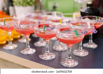 Pink alcoholic cocktail in sour glass with sprig of lavender pinned at it's rim with decorative clothe spin standing in row at outdoor cocktail party