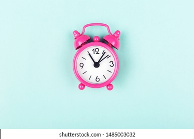Pink analog clock on turquoise background. Flat-lay, top view. Copy space for your text.
