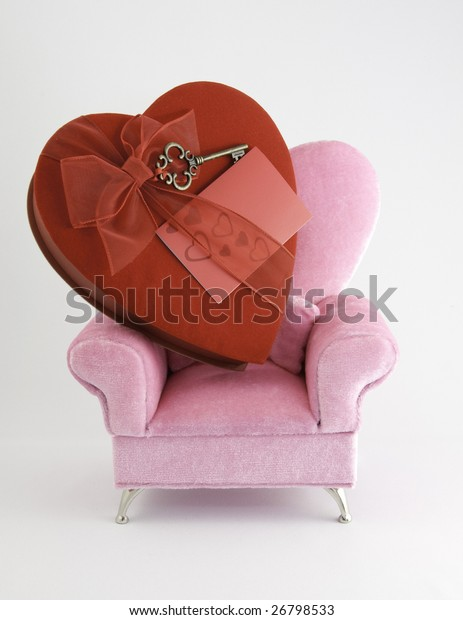 Pink arm chair with a big red heart of chocolates and a white background.
