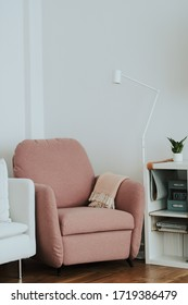 Pink armchair in a modern real decor near plants and a grey sofa