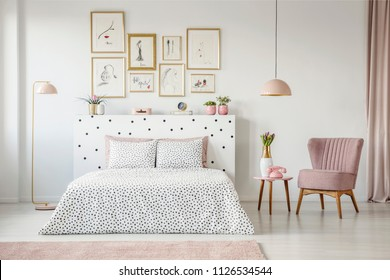 Pink armchair next to patterned bed in feminine bedroom interior with gallery of posters