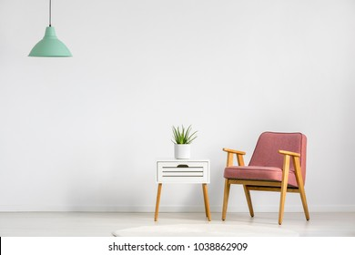 Pink armchair and wooden table on empty wall in simple living room interior