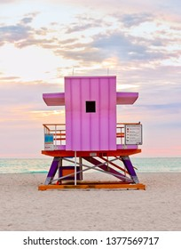 Pink art deco lifeguard stand on Miami South Beach at sunrise, life guard tower on coastal shoreline