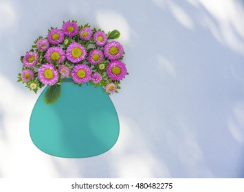 Pink aster flowers in a turquoise vase against a white background. real pink flowers with drawn blue turquoise vase. Flower pot isolated.
