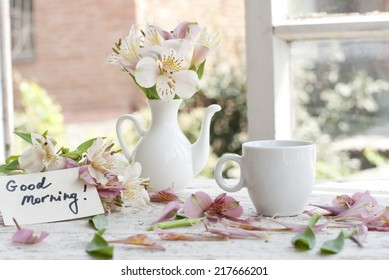 Pink Astromeria flowers in a white jar vase with good morning note spread around