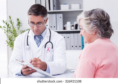Pink awareness ribbon against doctor explaining prescriptions to senior woman