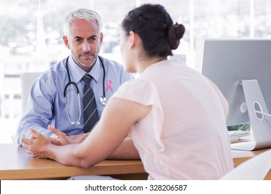 Pink awareness ribbon against patient explaining her painful to doctor