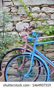 Pink and baby blue colored bicycle leaned against a stone brick.