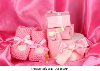 pink baby boots, pacifier, gifts on silk background