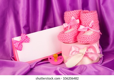 pink baby boots, pacifierd, postcard and gifts on silk background