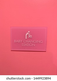 Pink baby changing station sign in pink