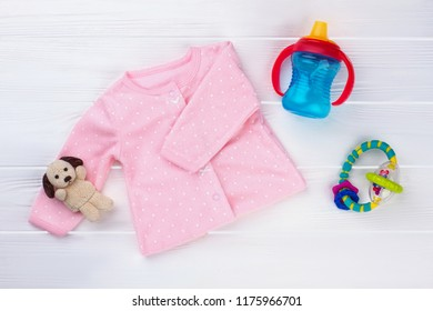Pink baby girl shirt and toys. Plush dog, bottle and rattle. White wooden desk background.