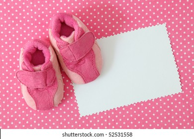 Pink baby shoes and blank note on spotted background