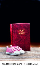 Pink baby shoes and Holy Bible with room for your type.