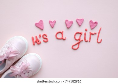 "Pink baby shoes or toddler shoes with ""It's a girl"" lettering or inscription, pink plasticine letters with plasticine hearts for newborn baby girl for baby shower party. Top view"