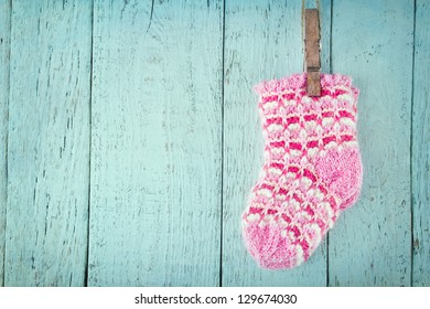 Pink baby socks on a blue wooden rustic background with copy space