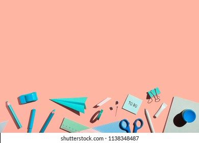 Pink background and blue school supplies. School abstract flat lay.