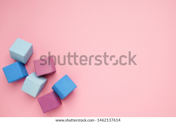 Pink background with colorful wooden cubes.Creativity toys. Children's building blocks.