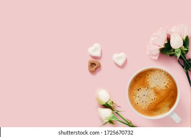 Pink background with a Cup of coffee surrounded by roses and pieces of sugar.