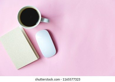 pink background desk table with laptop, cup of coffee and supplies.