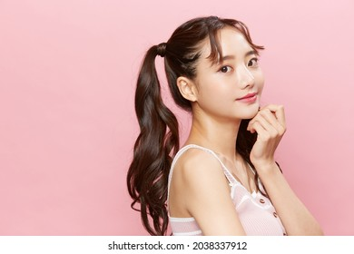 Pink background portrait of a young Asian woman with pigtails