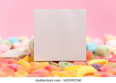 Pink background with sugary jellies and blank notepad. Place for your text. Cozy sweet background