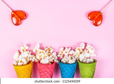 Pink background and sweets. Sparse popcorn and lollipops. Copy space. popcorn on a pink background. Popcorn and hearts